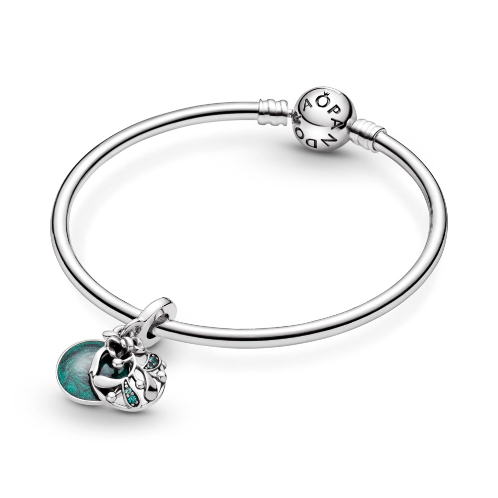 "Pandora Christmas Mistletoe Dangle Charm is hand-finished in sterling silver featured on the smooth Pandora moments Bangle. A front openwork mistletoe dangle is decorated with green stones that hangs at an angle. The back disc features hand-applied shimmering green enamel and the engraving: ""Meet me under the mistletoe."" on the back of the disk. The engraving ""Christmas wishes"" is featured on the side of the bail."