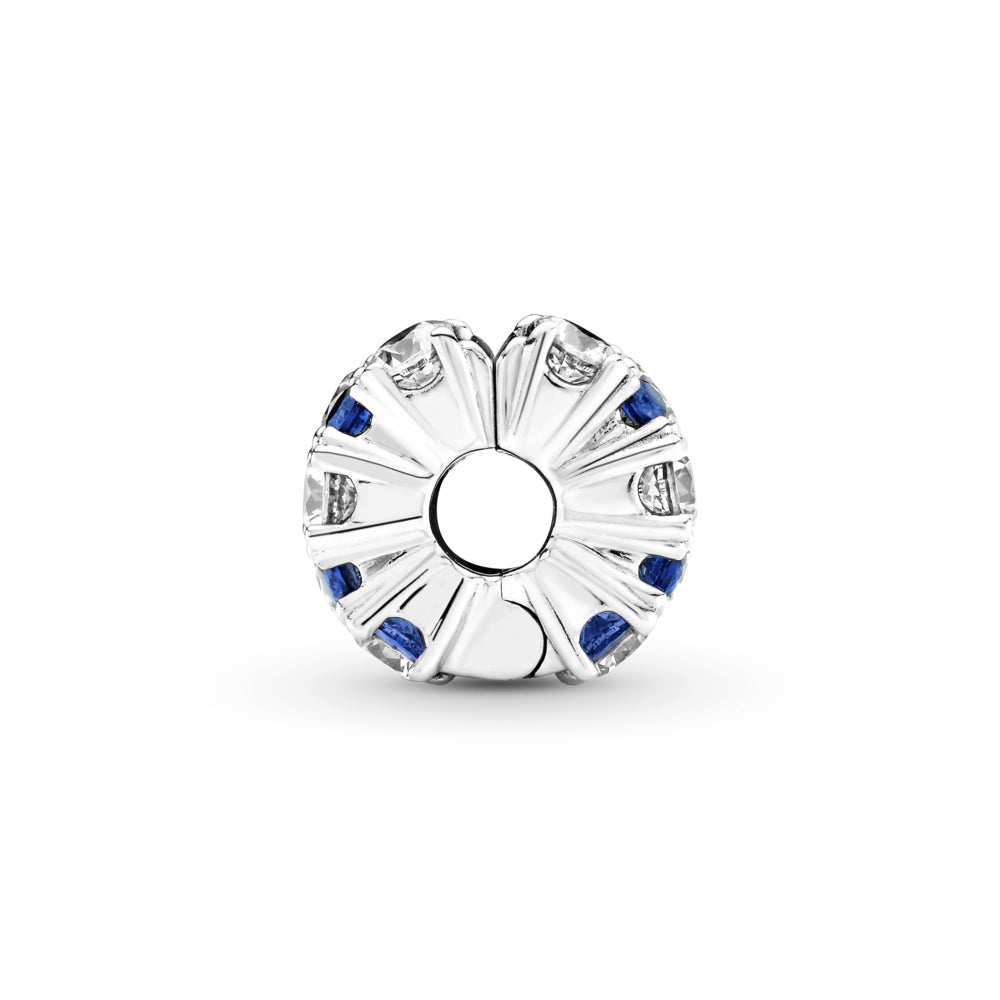 Profile view of Pandora Clear & Blue Sparkling Clip Charm. Hand-finished in sterling silver,the round clip features clear and stellar blue stones in various sizes along its outer edge. The silver on the side looks like star flares radiating from the clips opening.