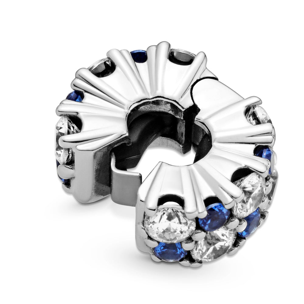 Close up of Pandora Clear & Blue Sparkling Clip Charm. Hand-finished in sterling silver,the round clip features clear and stellar blue stones in various sizes along its outer edge.  Shown open with interior black silicone grip inside.