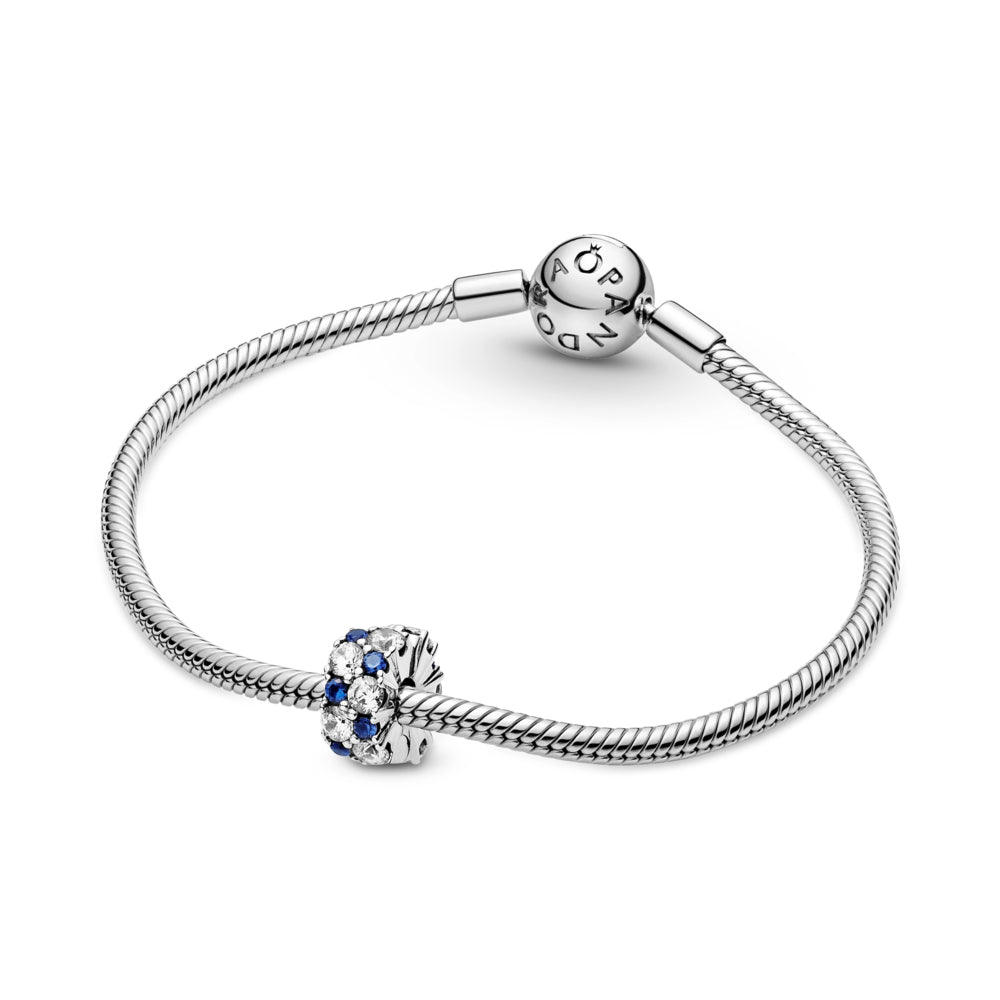 Pandora Clear & Blue Sparkling Clip Charm featured on silver snake chain moments bracelet. Hand-finished in sterling silver, the round clip features clear and stellar blue stones in various sizes along its outer edge.