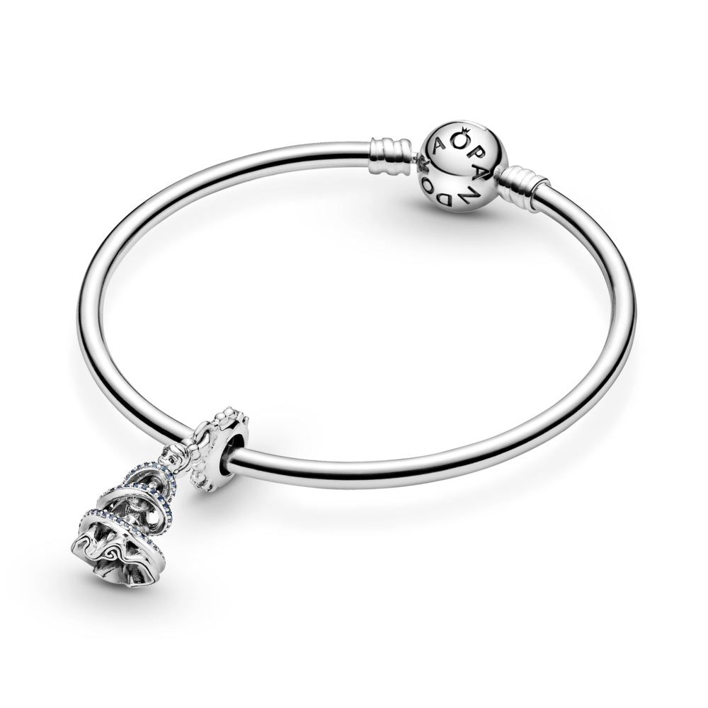 Pandora Disney Cinderella Magical Moment Dangle Charm featured on a smooth Pandora Moments bangle bracelet. Hand-finished in sterling silver, this design includes the spinning princess dressed in a ball gown and surrounded by a swirl decorated with blue stones. Includes a beaded bail with clear stones.