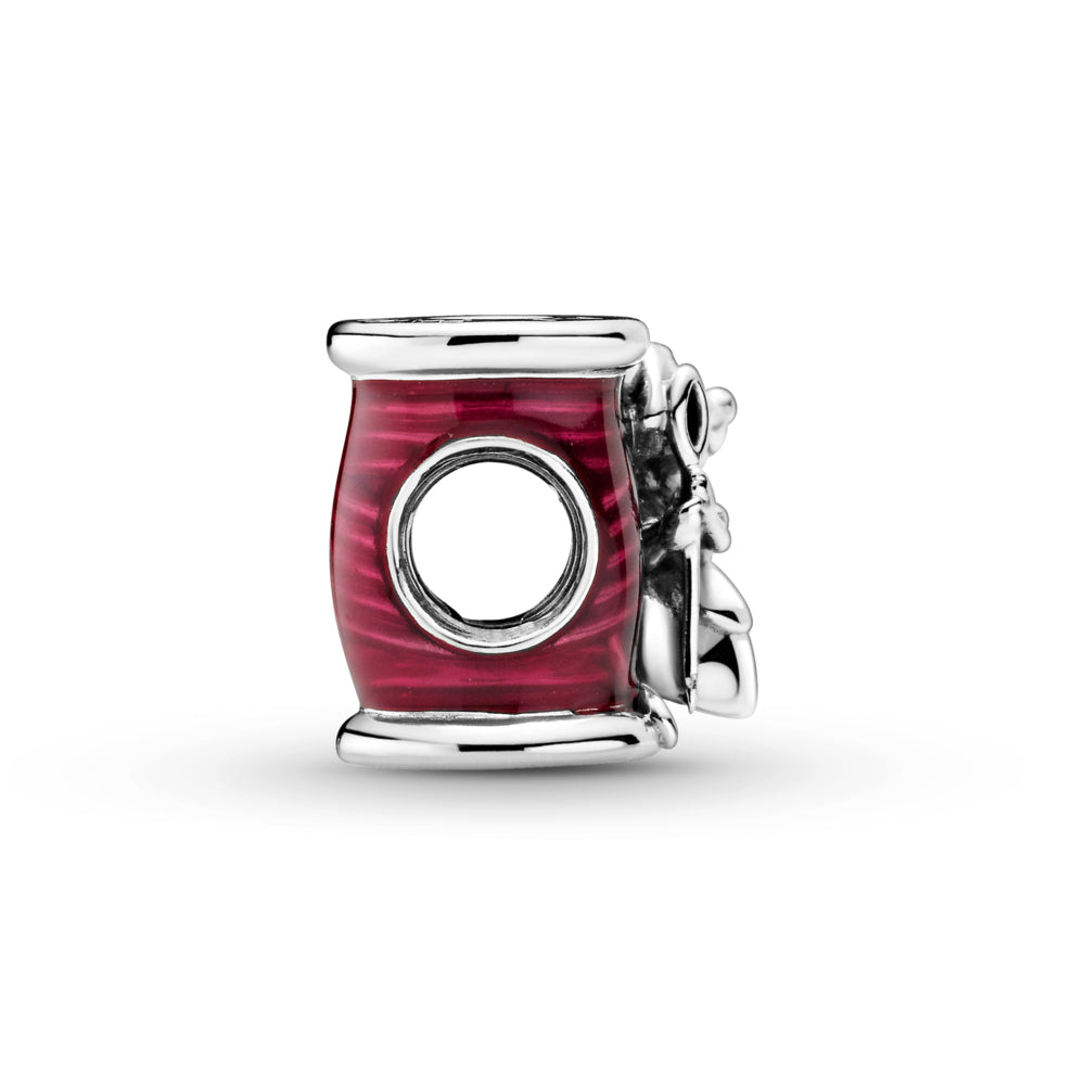 Pandora Disney Cinderella Suzy Mouse Needle & Thread Charm in sterling silver. Suzy is holding a needle while hugging a thread spool decorated with hand-applied transparent cerise enamel to highlight the thread details.