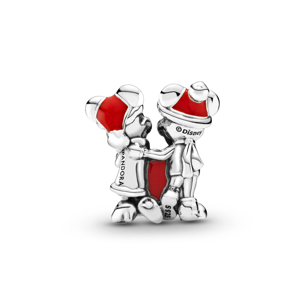 Back side of Pandora Disney Mickey & Minnie Mouse Present Charm in sterling silver.  Mickey & Minnie are holding a red present. Mickey is wearing a scarf and touching Minnie on her shoulder. Both have grooved eyes and eyelashes to highlight their features and are wearing Christmas hats in red enamel.