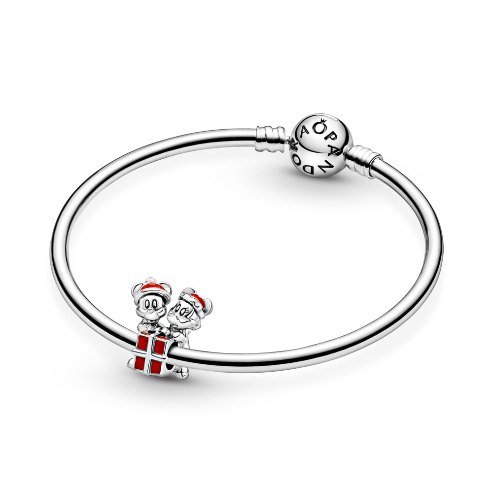 Pandora Disney Mickey & Minnie Mouse Present Charm in sterling silver featured on Pandora Moments Bangle.  Mickey & Minnie are holding a red present. Mickey is wearing a scarf. Both have grooved eyes and eyelashes to highlight their features and are wearing Christmas hats in red enamel.
