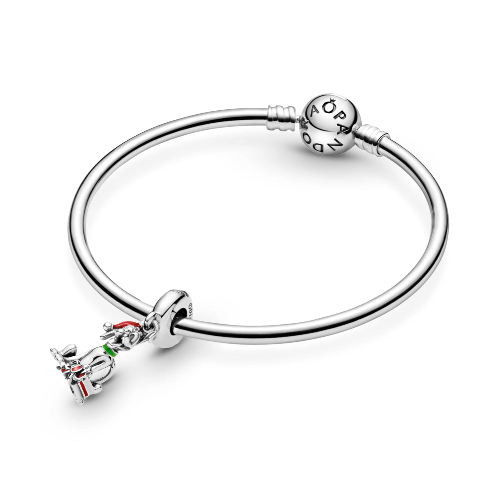 Pandora Disney Pluto Christmas Gift Charm in sterling silver is featured on a silver Pandora Moments bangle bracelet. Pluto is sitting with his tongue out in front of a red present with a bow, wearing a green collar, and a red Christmas hat. The silhouette of Mickey Mouse is featured on the bail with a stone set in the center.