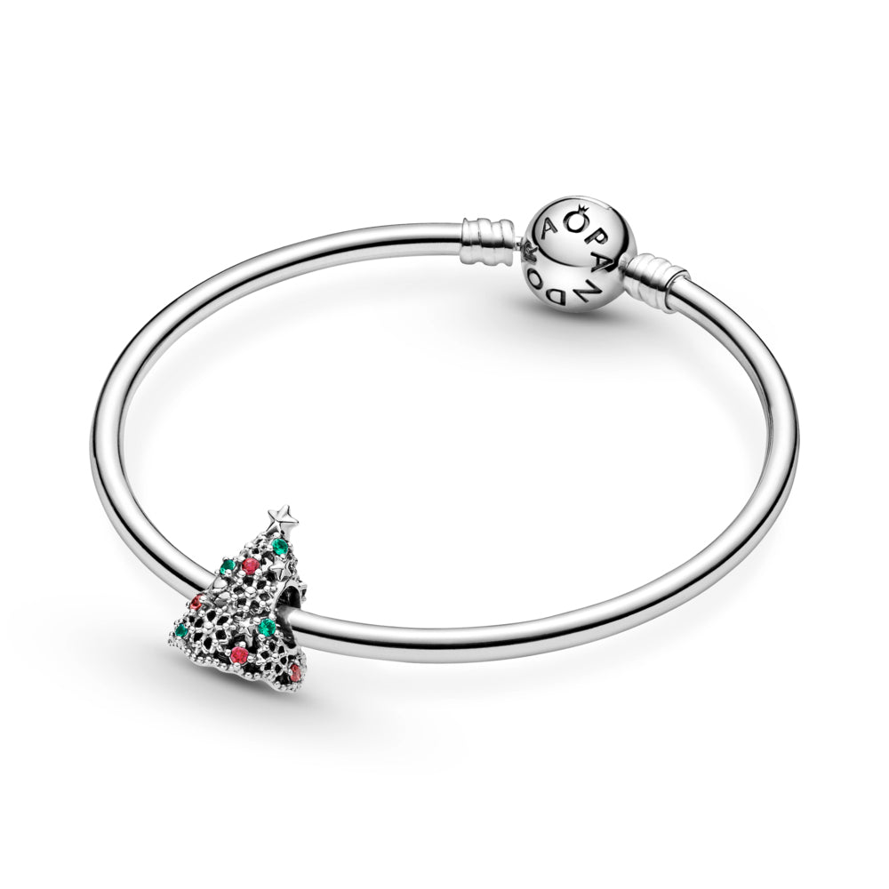 Pandora Glitter Christmas Tree Charm in sterling silver featured on Pandora Moments bangle bracelet. The openwork Christmas tree has stars, hearts, snowflakes, red, and green stones for decorations, including a 5-point star on top and a cut-out snowflake underneath the tree