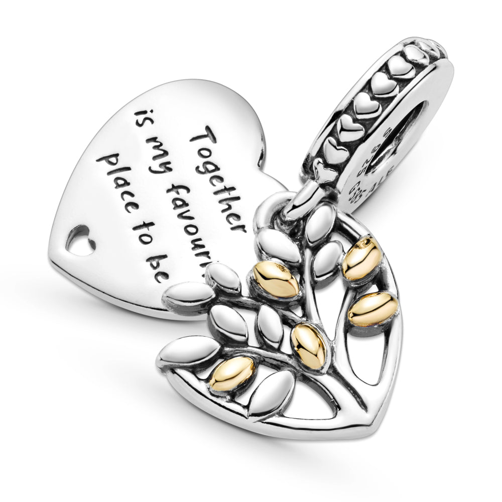 "Close up of Pandora Two-Tone Family Tree Heart Dangle Charm in sterling silver and 14k gold, this openwork design features a tree motif with 14k gold leaves layered on top of a polished heart-shaped disc with an engraving ""Together is my favorite place to be""."