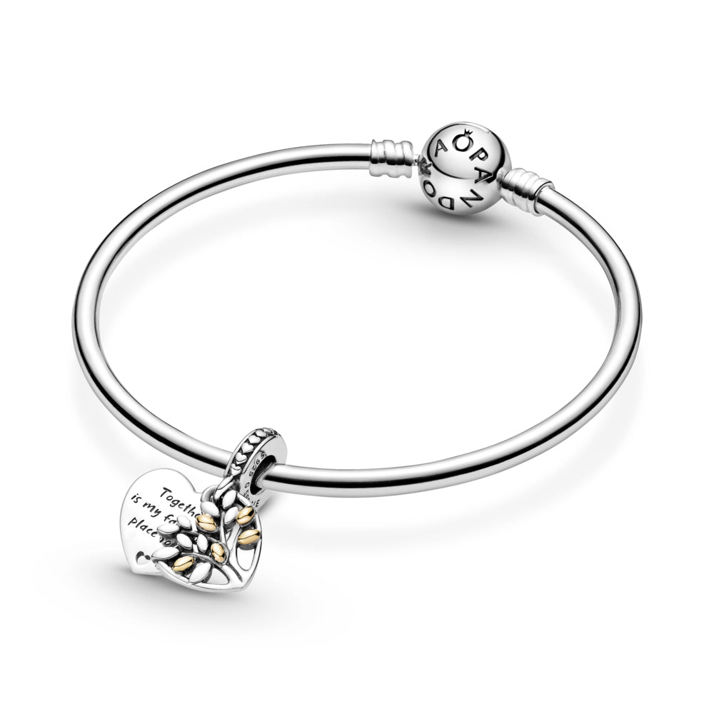 "Pandora Two-Tone Family Tree Heart Dangle Charm in sterling silver and 14k gold featured on Silver Pandora Moments bangle bracelet. This openwork design features a tree motif with 14k gold leaves layered on top of a polished heart-shaped disc with an engraving ""Together is my favorite place to be""."
