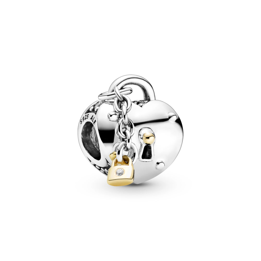 Pandora Two-Tone Heart and Lock Charm in sterling silver and 14k gold. The heart-shaped design includes a padlock and slightly raised keyhole with 14k gold detailing at the top surrounded by 4 silver nails, and clear stones decorating the top of the charm. A small 14k gold padlock dangles from a chain.