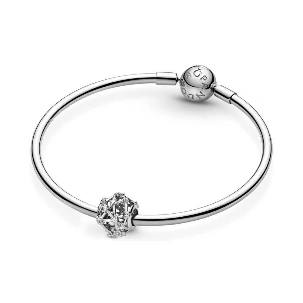 Pandora Openwork Star Constellations Charm in sterling silver featured on moments smooth bangle bracelet. Clear stones are set along the charm's rounded openwork lines to mimic the formation of the stars in space.