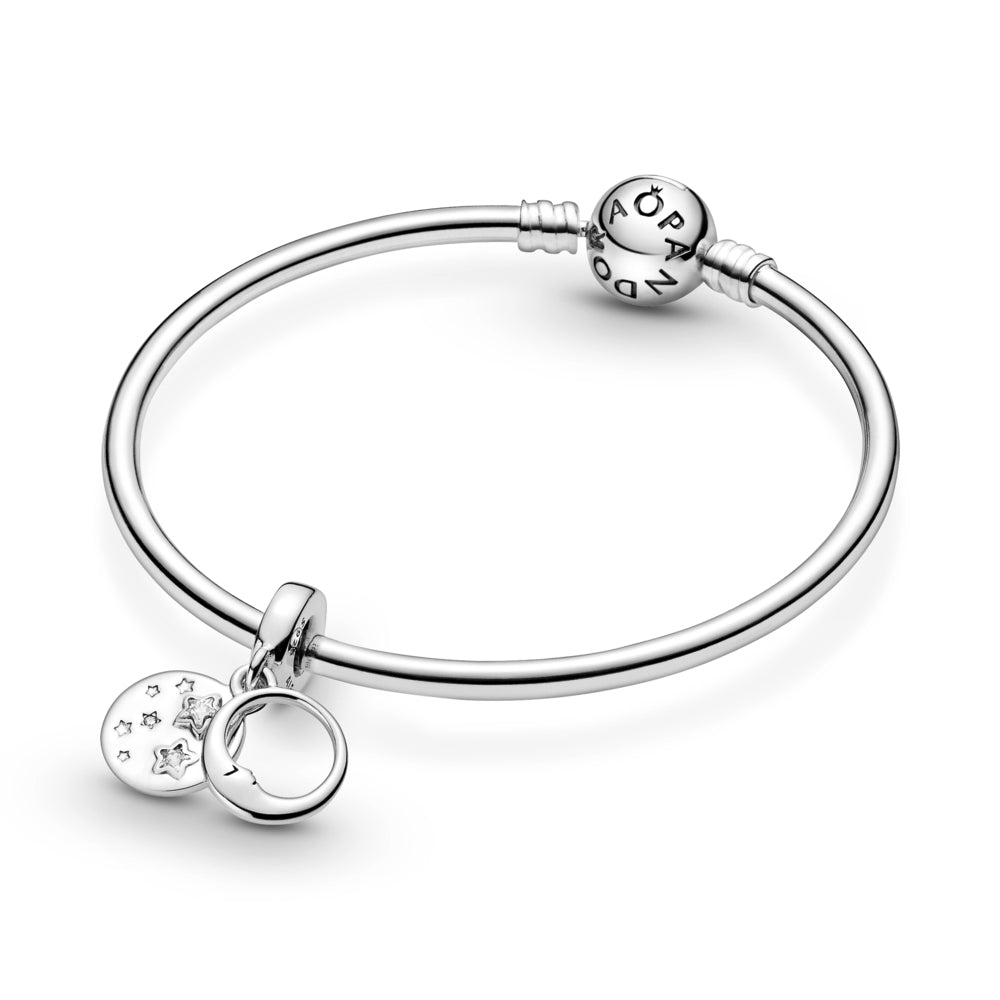 "Pandora Sleeping Moon and Stars Dangle Charm in sterling silver on smooth moments bangle bracelet. The front dangle has an open circle with a sleeping crescent moon with a face on both sides. The back disc includes stars, some are set with round or star-shaped stones. ""You are my universe"" is engraved on the back with cut-out stars."