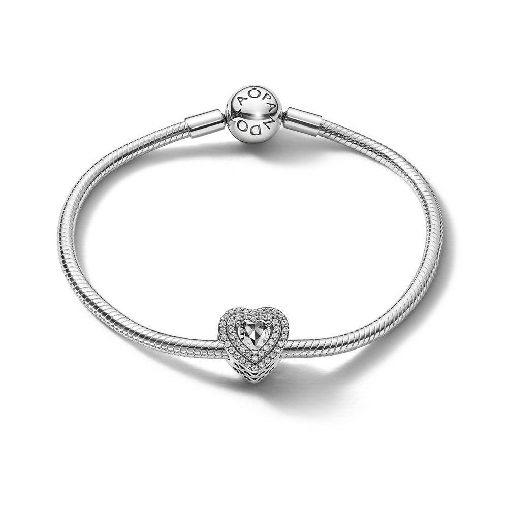 Pandora Sparkling Heartfelt Holiday Bracelet Gift Set in sterling silver. The set includes the classic Pandora Moments Snake Chain Bracelet and the Sparkling Levelled Hearts Charm. The charm has an elevated heart-shaped clear cubic zirconia stone surrounded by two layers of pave stones.