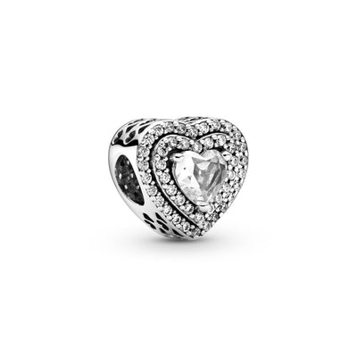 Pandora Sparkling Leveled Hearts Charm in sterling silver. This charm has an elevated heart-shaped stone at the center outlined by two rows of clear stones. A cut-out heart pattern is featured on the sides.