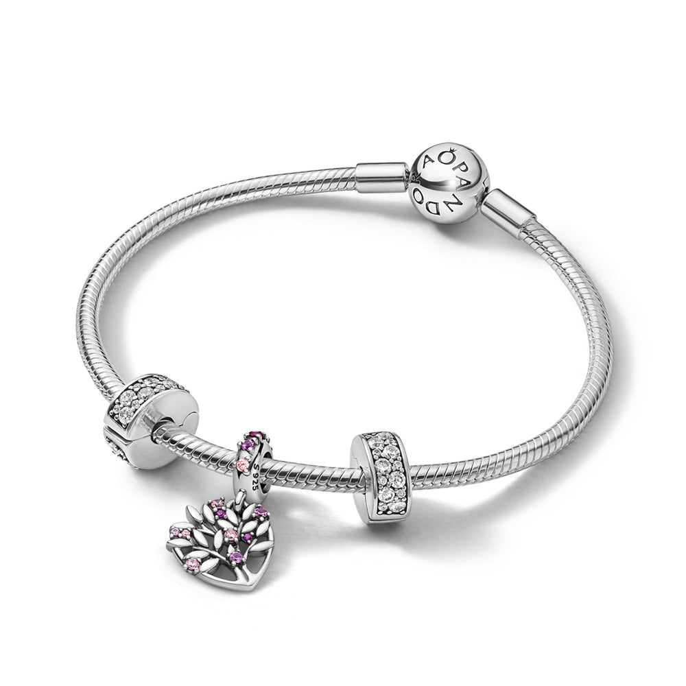 Pandora Sparkling Pink Heart Family Tree Bracelet Gift Set features a sterling silver Pandora Moments Snake Chain Bracelet, with 2 Shining Elegance Clips with dazzling cubic zirconia, and the Heart Family Tree Dangle Charm with soft pink and ruby-colored stones is the centerpiece.