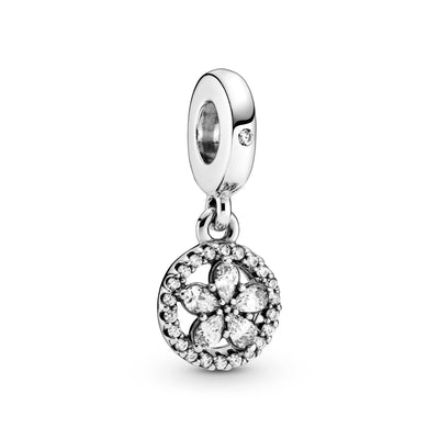 Pandora Sparkling Snowflake Circle Dangle Charm in sterling silver. The charm features clear stones in the form of a raised star-like snowflake formation inside a circle decorated with clear cubic zirconia. One clear stone featured on the bail.