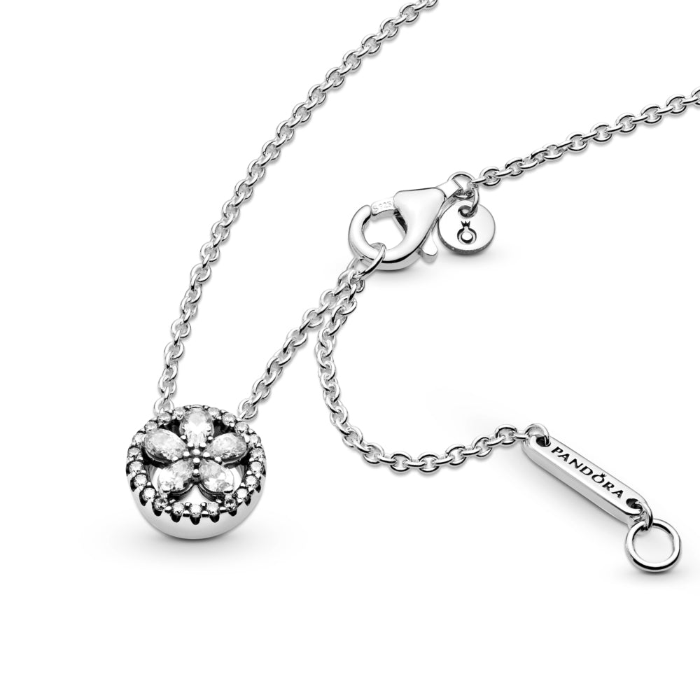 Pandora Sparkling Snowflake Necklace in sterling silver. The necklace features clear stones in the form of a star-like snowflake formation inside a circle decorated with clear cubic zirconia. One pear-shaped stone dangles from the end of the chain and a Pandora crown O monogram logo tag featured by the clasp.