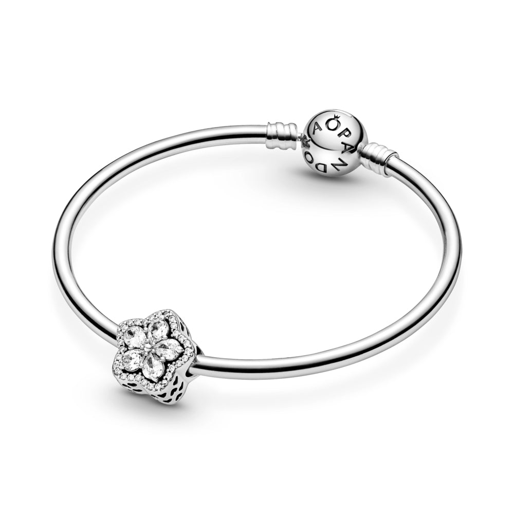 Pandora sparkling Snowflake Pavé Charm in sterling silver featured on smooth moments bangle bracelet. The pear-shaped stones are set in the form a snowflake star at its center and outlined with clear cubic zirconia and cut-out hearts along the sides.