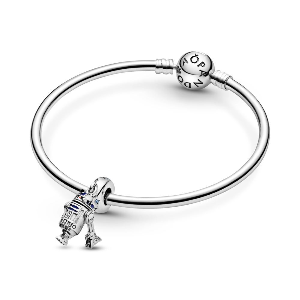 Pandora Star Wars R2-D2 Dangle Charm featured on a Pandora Moments smooth sterling silver bangle. The charm is sterling silver with blue, red, and black enamel detailing. The bale has blue czs with 4 point cut out stars with a life like detailed R2-D2  replica charm