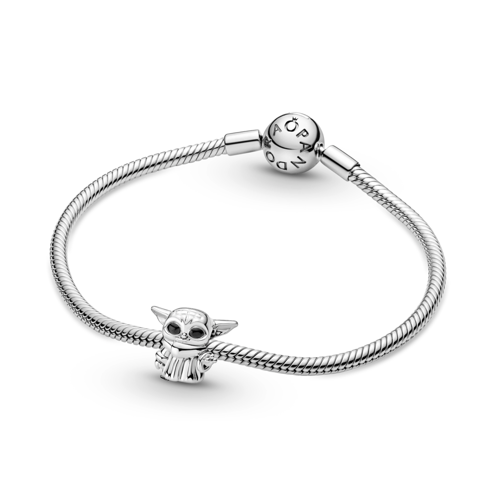 Baby Yoda 3D Pandora Star Wars charm is shown featured on the Pandora Moments Snake chain bracelet in sterling silver.   The Child  from The Mandalorian TV series on Disney+ is standing with his left hand raised, has black enamel eyes, and is wearing his signature cloak.