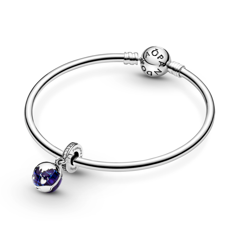 "Pandora Unicef Our Blue Planet dangle charm in sterling silver with blue enamel ocean details and a channel set sparkling CZ bail with the engraving ""Supporting Young Voices"".  Shown on Pandora moments sterling silver bangle."