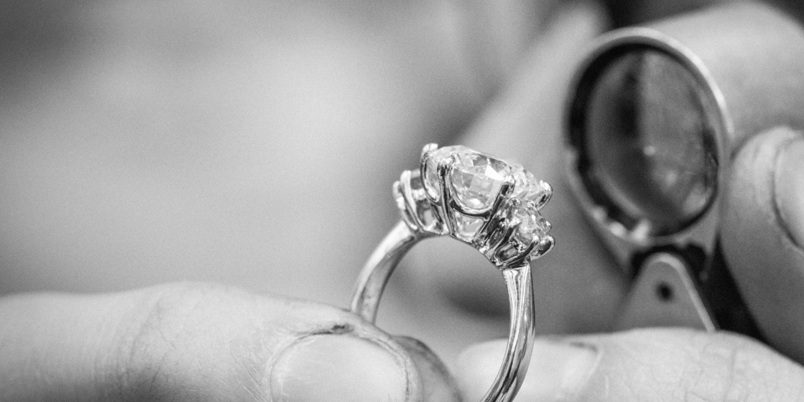 Jeweller looking at a three stone lab grown diamond engagement ring through a jewellers loupe