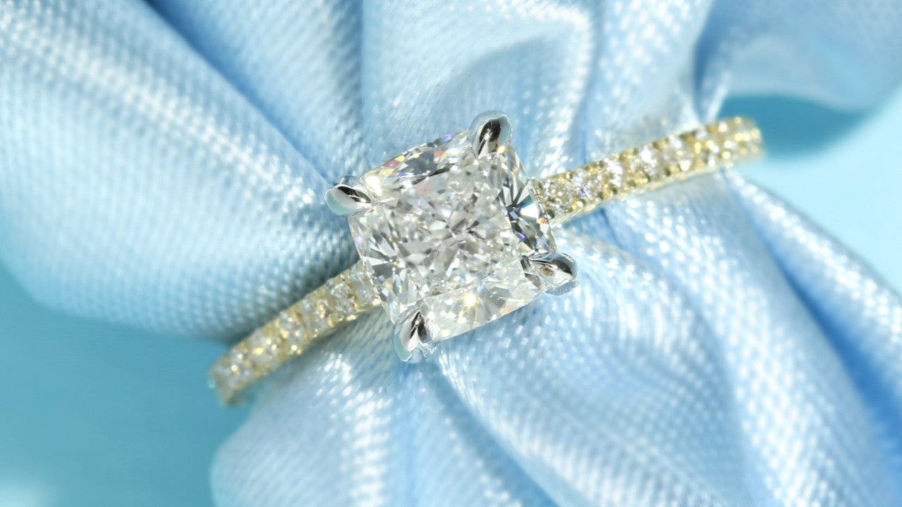 Cushion cut lab grown diamond engagement ring in yellow gold on a blue ribbon backgroud