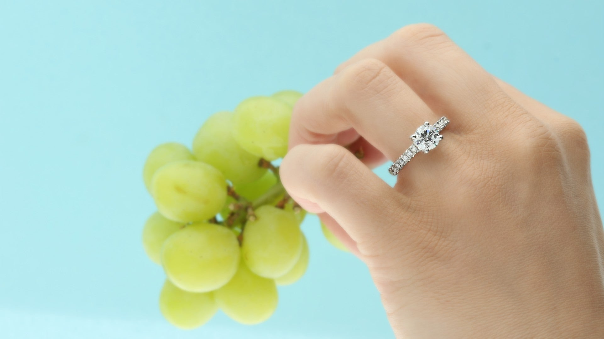 hand modeling lab grown diamond engagement ring holding bunch of green grapes