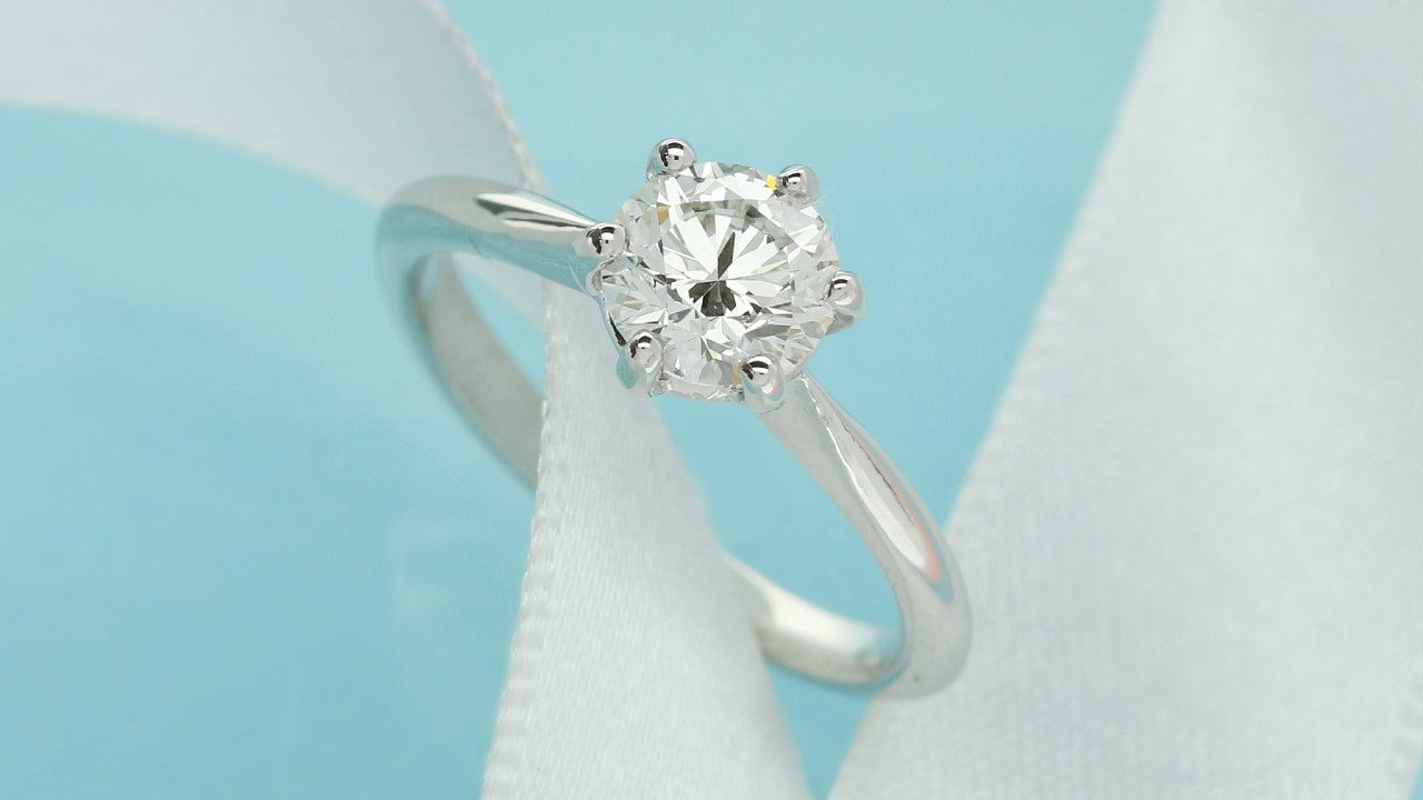 Round brilliant cut lab grown diamond solitaire engagement ring sitting on white ribbon