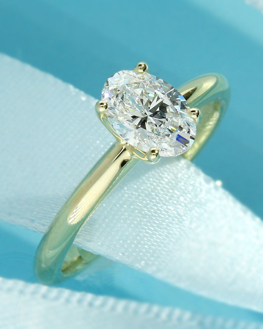 Yellow gold solitaire engagement ring set with an oval lab grown diamond