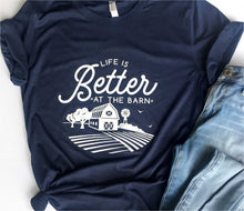 Load image into Gallery viewer, navy blue short sleeve graphic tshirt that reads life is better at the barn with a barn scene.