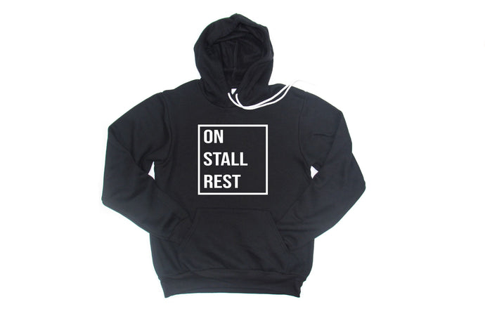 Dark grey fleece hooded sweatshirt prints with the words On Stall Rest