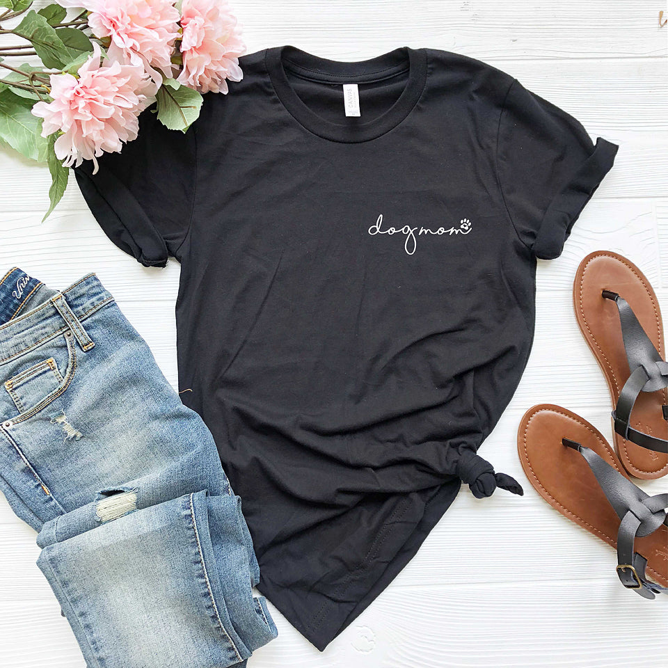 black  short sleeve tshirt printed with dog mom in lower case script writing with a little paw print in white ink placed over the left chest