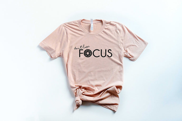 peach short sleeve tshirt with black lettering that reads don't lose focus. The o in focus is a camera shutter