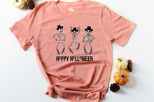 Load image into Gallery viewer, orange short sleeve graphic tee printed with 3 dancing skeletons wearing cowboy hats and boots that reads Happy Halloween