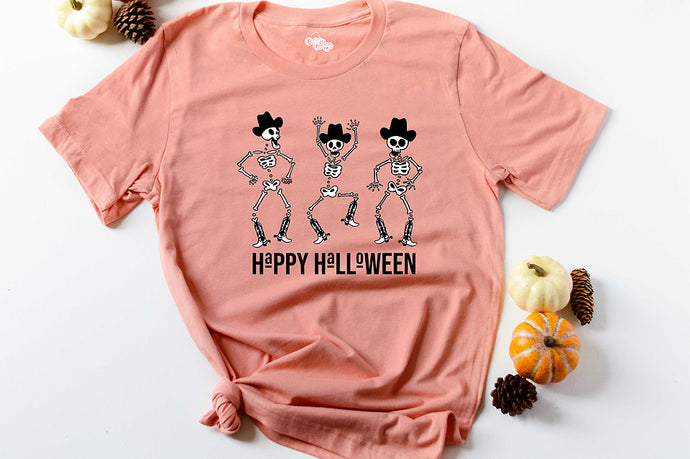 orange short sleeve graphic tee printed with 3 dancing skeletons wearing cowboy hats and boots that reads Happy Halloween
