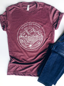 maroon short sleeve tshirt printed with a mountain scene and a silhouette horse and rider with the saying Go Ride and Explore arched across the top.