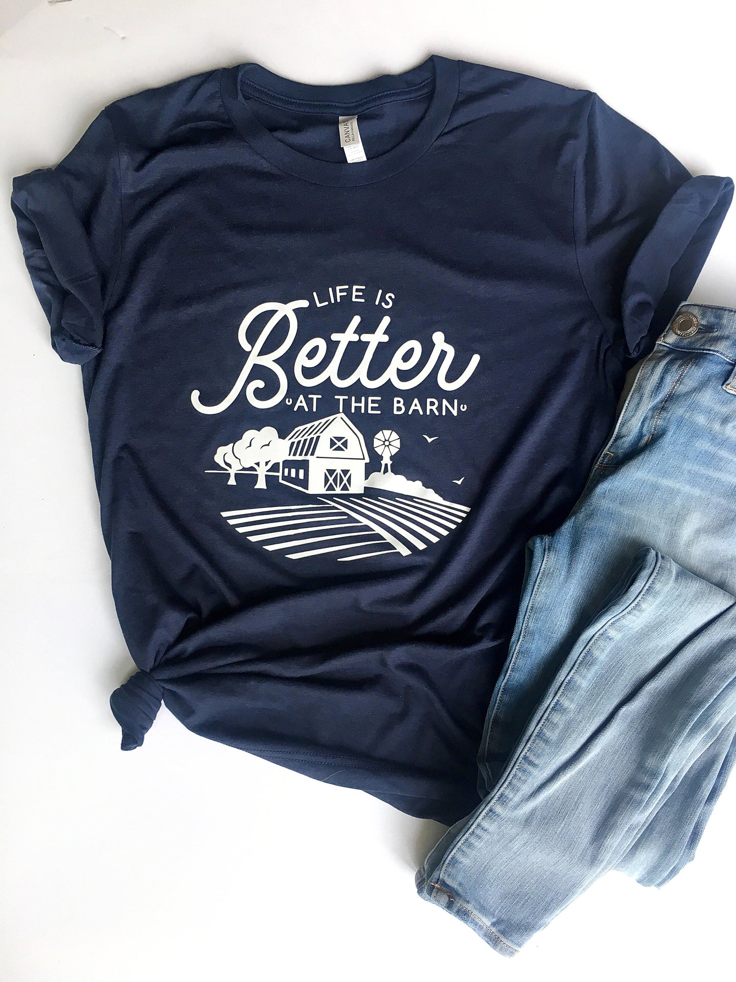 navy  blue short sleeve graphic tshirt that reads life is better at the barn with a barn scene.