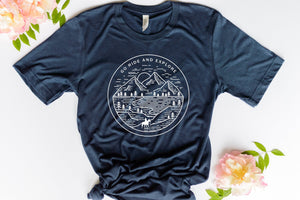 Navy blue short sleeve tshirt printed with a mountain scene and a silhouette horse and rider with the saying Go Ride and Explore arched across the top.