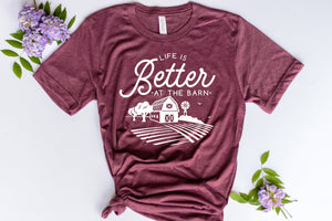 maroon short sleeve graphic tshirt that reads life is better at the barn with a barn scene.
