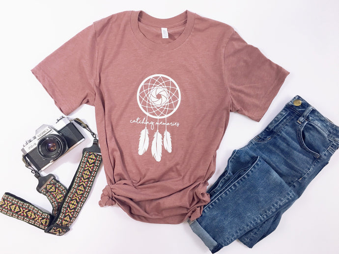 dusty rose pink short sleeve tshirt printed with a white dream catcher, the center being a camera shutter, that reads catching dreams in script lettering
