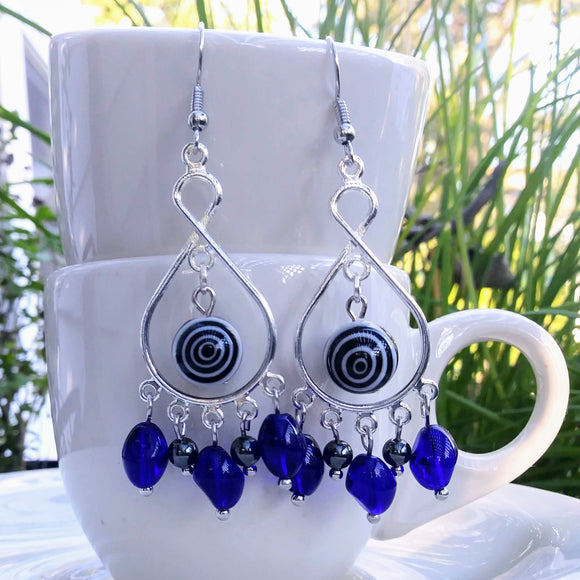 Silver-toned chandelier frame earrings with bulls-eye beads and accents of cobalt blue glass dangle from a stack of espresso cups on a balcony