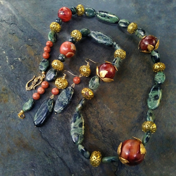 A natural stone necklace-earring set in green kambaba jasper and orange agate lies on a dark gray stone slate.