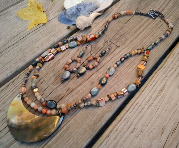 A beaded agate and shell multi-strand necklace with matching earrings lies across raw wood planks.