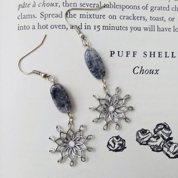 Silver wire snowflakes hang from gray spotted quartz dangle earrings, against a backdrop of an old pastry cookbook