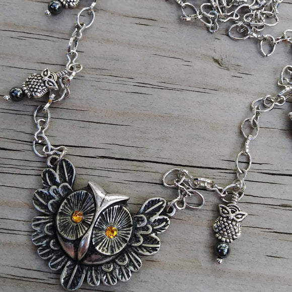 A silver-toned owl pendant with amber-colored crystal eyes, on a long chain with small owl dangles