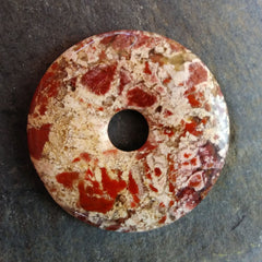 Brecciated jasper stone donut mostly cream with bits of rusty red