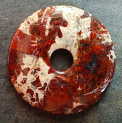 Brecciated jasper stone donut mostly red with a swath of cream