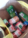 A grocery bag partially filled with boxes of pasta and canned beans