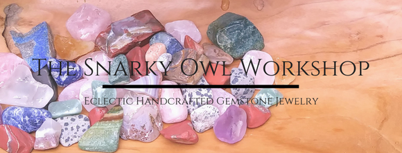 The Snarky Owl Workshop: Eclectic handcrafted gemstone jewelry. Backdrop of various free-form natural stones against wood