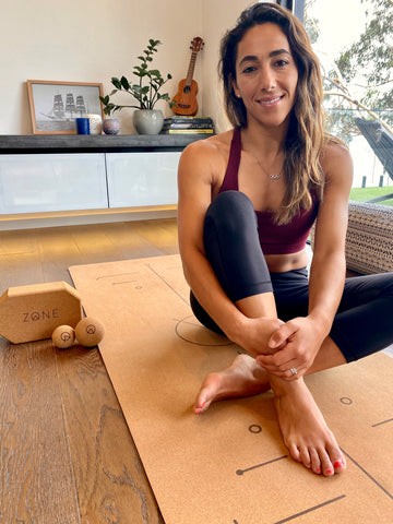 Lydia Lassila sitting on Cork Yoga Mat with her Zone by Lydia range of sustainable cork products